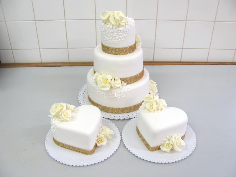 svatební dort se zlatým zdobením a děkovacími dorty